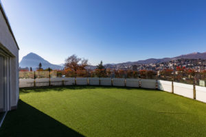 Terrace with synthetic lawn overlooking the city of Lugano in Switzerland. Nobody inside