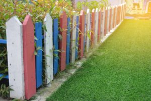 Colorful fence and green artificial grass field